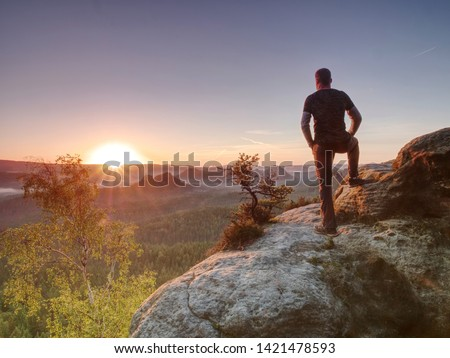 Man on the rock empire with hands in trousers pocket  watch over the misty morning valley to rising sun at horizon. #1421478593