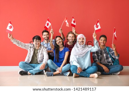 Group of students with Canadian flags sitting near color wall #1421489117