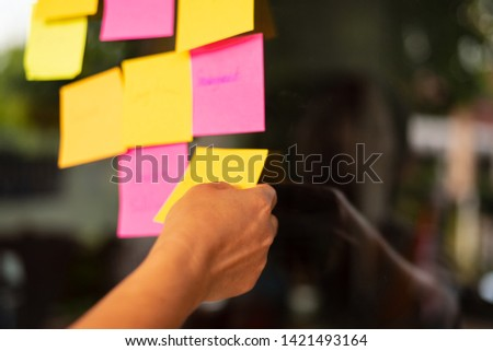 Close up woman hand holding note sticky for brainstorm and share idea strategy workshop business.Brainstorming concept. #1421493164