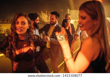 Shot of two male friends cheering with drinks in the club. Selective focus #1421508077