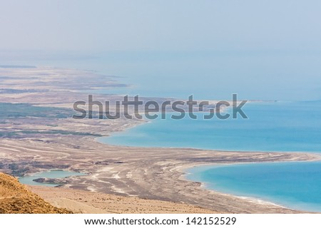Panoramic view on wavy Dead Sea shore and mountain slope in morning haze with glowing at dawn. Judean desert, Metzoke Dragot, Israel.  #142152529