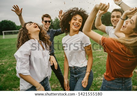 Group of five friends having fun at the park - Millennials dancing in a meadow among confetti thrown in the air - Day of freedom and carefree Royalty-Free Stock Photo #1421555180