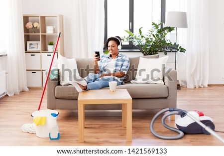 household and technology concept - happy african american woman or housewife in headphones with smartphone resting after home cleaning, listening to music and singing #1421569133