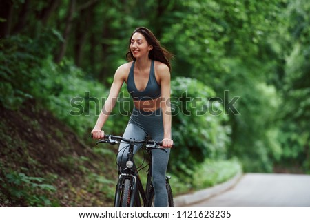 Cheerful mood. Female cyclist on a bike on asphalt road in the forest at daytime. #1421623235