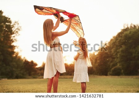 Keep holding it like that. Mother and daughter have fun with kite in the field. Beautiful nature. #1421632781