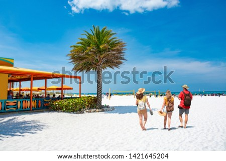 Family walking on beautiful white sand beach on summer vacation in Florida Volleyball nets, beach umbrellas and green ocean in background.  Gulf of Mexico, Clearwater Beach, Florida, USA. #1421645204