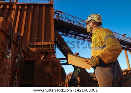 Miner engineer planer holding a planing book while looking up crashing chute during shut down operation Sydney mite site, Australia #1421683301