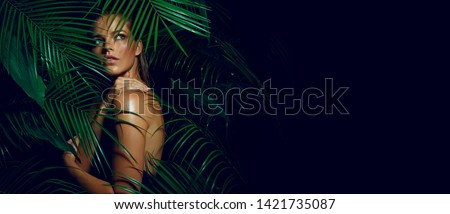 A beautiful tanned girl with natural make-up and wet hair stands in the jungle among exotic plants #1421735087