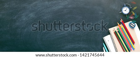 School stationary on blackboard. Notebooks, pens, pencils, alarm clock, red apple and other tools. Banner with place for text.