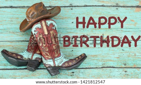 teal and brown cowboy boots and hat laying flat on a wooden teal background with happy birthday in brown text
