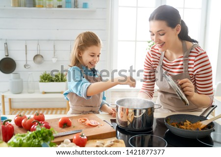 Healthy food at home. Happy family in the kitchen. Mother and child daughter are preparing proper meal. #1421877377