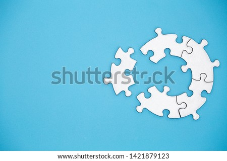 Unfinished white jigsaw puzzle pieces on blue background, The last piece of jigsaw puzzle, Copy space. #1421879123