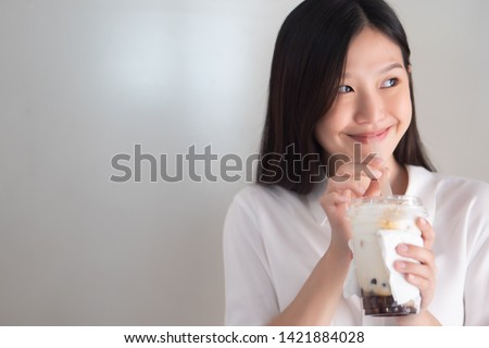 Happy smiling asian woman drinking iced bubble milk tea; aka boba tea, pearl milk tea, tapioca tea; Asian exotic beverage concept #1421884028