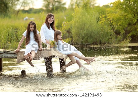 Family portrait of a smiling and cheerful mother and two daughters on a picnic at the lake #142191493