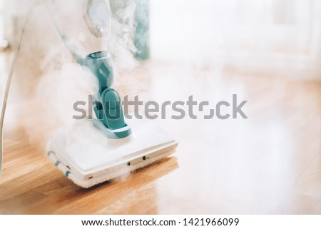 Steam cleaner mop cleaining floor. Banner with copy space. Cleaning service concept. Royalty-Free Stock Photo #1421966099