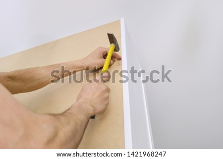 Installation of furniture. Closeup of workers hand with professional tools and furniture details. #1421968247