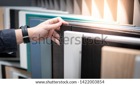 Male hand choosing cabinet panel materials or countertops for built-in furniture design. Shopping furniture and decoration. Home improvement concept Royalty-Free Stock Photo #1422003854