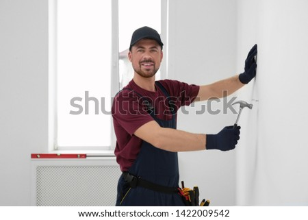 Handyman in uniform working with hammer indoors. Professional construction tools #1422009542