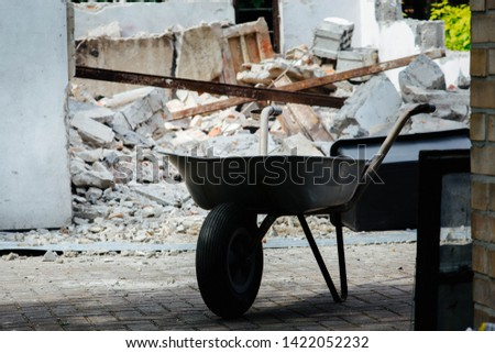 wheelbarrow on the background of demolition of a garage - construction rubble #1422052232