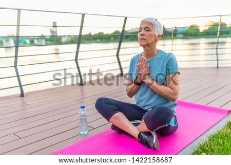Yoga at park. Senior woman sitting on yoga mat. Concept of calm and meditation. Beautiful woman meditating on a boardwalk at sunset. Beautiful mature woman practice yoga in summer park #1422158687