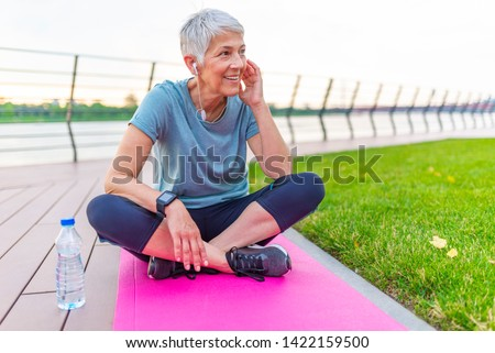 Senior Woman Resting After Exercises. Senior lady prefers healthy lifestyle. Happy senior lady relaxing after training. Mature woman resting on mat after exercise  #1422159500