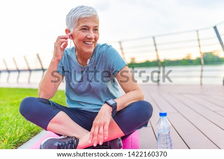 Senior Woman Resting After Exercises. Senior lady prefers healthy lifestyle. Happy senior lady relaxing after training. Mature woman resting on mat after exercise  #1422160370