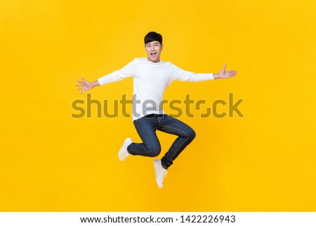 Young happy Korean teen jumping welcomely isolated on yellow studio background #1422226943
