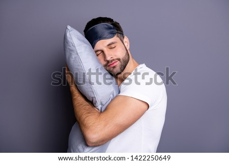 Close-up portrait of his he nice attractive bearded guy holding in hands pillow drowsiness going to bed sleeping quietly calmly isolated over gray pastel violet purple background #1422250649
