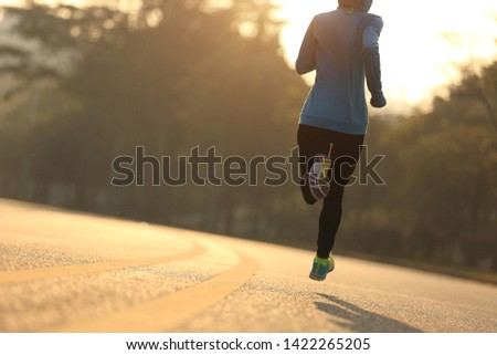 Young fitness woman runner running on sunrise road #1422265205