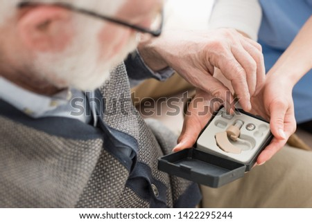 High angle view of elderly man looking at box with hearing aid #1422295244