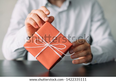 Office delivery service. Cropped shot of business man in shirt sitting at desk with red gift box. Copy space. Royalty-Free Stock Photo #1422335111