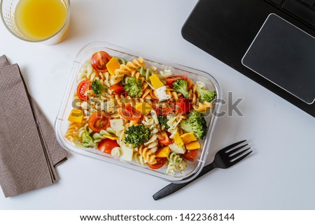 Healthy food in lunch box, on working table with laptop .Ensalada de pasta brocoli con queso y verduras. eating at workplace. Home food for office concept  Royalty-Free Stock Photo #1422368144