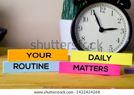 Your Daily Routine Matters. Handwriting on sticky notes in clothes pegs on wooden office desk #1422424268