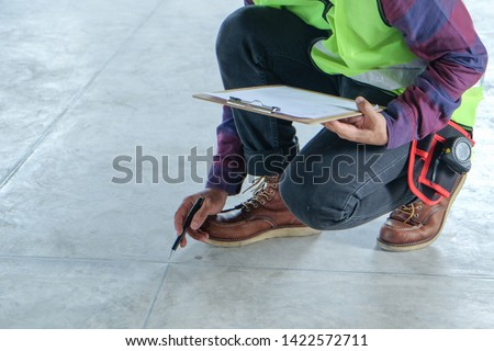 Inspector or engineer is checking and inspecting floor appearance and pointing to the surface. Inspection concept #1422572711