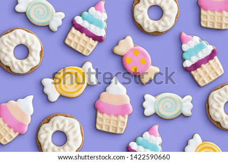 Cookies variety pattern on a pastel background. Various cookie shapes (cupcake, candy, donut). Top view.