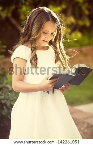 Cute little girl reading the Bible #142261051