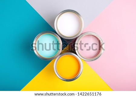 Four open cans of paint on bright symmetry background. Yellow, white, pink, turquoise colors of paint. Place for text. Renovation concept.