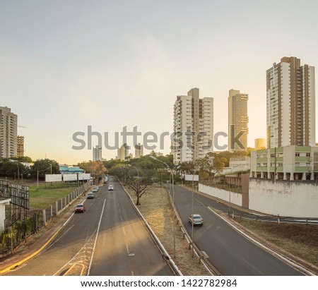 Two lanes avenue with few cars, trees, blank advertising billboards, and buildings around. Sunset at the large avenues of the capital city Campo Grande - MS, Brazil. Ricardo Brandao avenue. #1422782984
