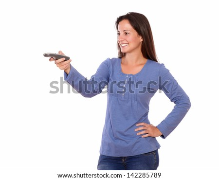 Portrait of a lovely young female pointing remote control while standing on white background #142285789