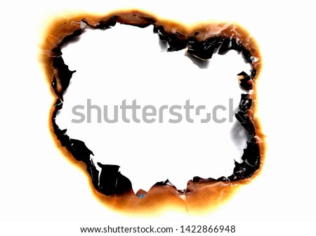burned hole on a white paper background Royalty-Free Stock Photo #1422866948