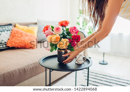 Woman puts vase with flowers roses on table. Housewife taking care of coziness in apartment. Interior design and decor #1422894068