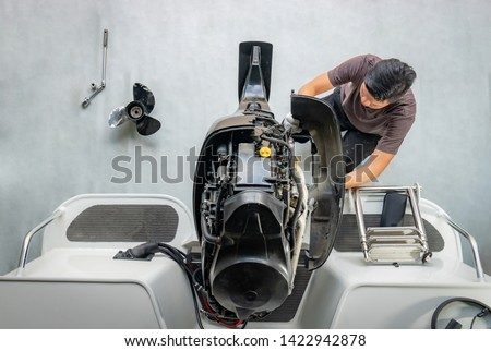 Repairing engines on aluminum boats , The technician is removing the boat parts to make the paint #1422942878
