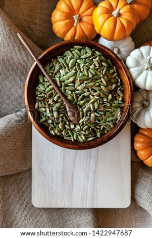 Full bowl of pumpkin seeds closeup on a cutting board with colorful pumpking around - Image #1422947687