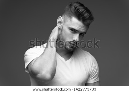 young man with a beard. A man in a t-shirt. Male portrait on a gray background. Stylish man. black and white photo. Sports man. male fitness model. studio portrait #1422973703