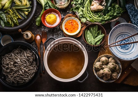 Various asian food ingredients for tasty soba noodles soup around cooking pot with delicious miso broth or stock on rustic kitchen table background, top view. Asian cuisine background. Healthy eating