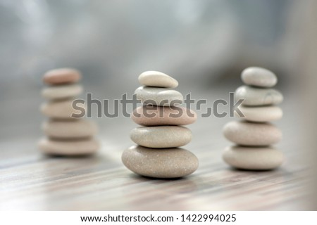Harmony and balance, three cairns, simple poise pebbles on wooden light white gray background, simplicity rock zen sculpture, river stones in towers #1422994025
