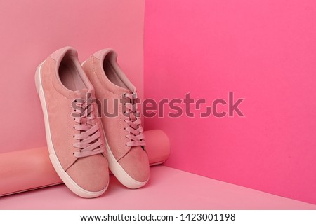 Comfortable sneakers and paper roll on color background, space for text Royalty-Free Stock Photo #1423001198