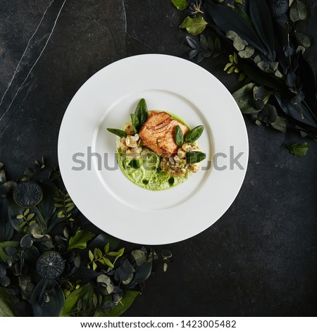 Exquisite Serving White Restaurant Plate with Fillet of Salmon 48 Degrees, Green Peas Cream and Burnt Cauliflower Top View. Stylish Italian Seafood Dish on Natural Black Marble Background #1423005482