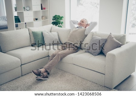 Full length body size photo amazing he him his aged man overjoyed calm hands arms behind head day off imaginary flight wear white shirt waistcoat pants sit cozy divan flat house living room indoors #1423068506
