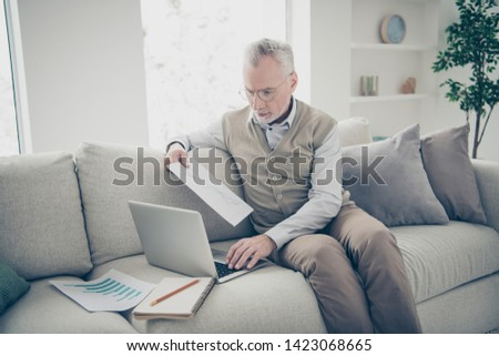 Close up side profile photo amazing he him his aged man hand arm notebook search analyzer check information charts stats wear white shirt waistcoat pants sit cozy divan flat house living room indoors